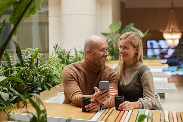 Casal feliz sentado à mesa do restaurante tomando café e usando o celular, relembrando seus momentos felizes