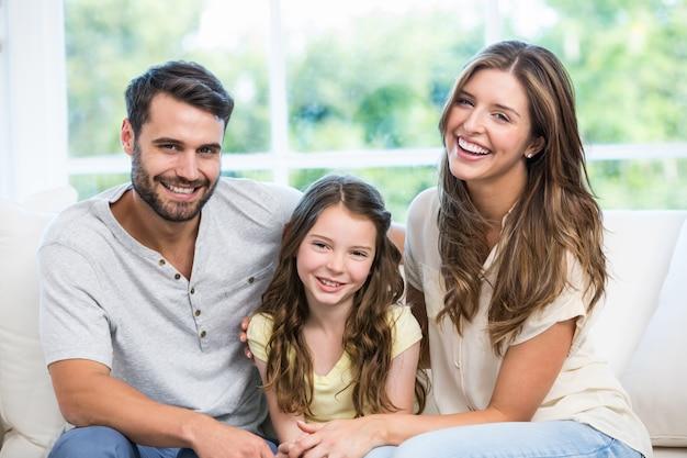 Casal feliz sentado com a filha no sofá