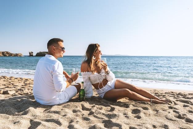 Casal feliz sentado com champanhe na praia.