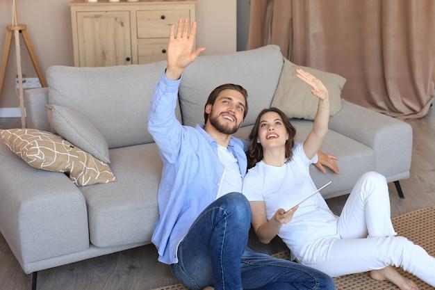 Casal feliz sentado e planejando a nova decoração da casa em casa com um tablet, renovação e design de interiores para a nova casa.
