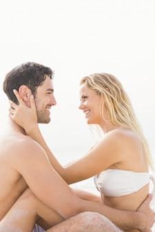 Casal feliz sentado e se abraçando