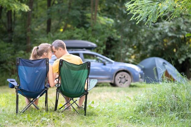 Casal feliz sentado em cadeiras no acampamento, abraçando uns aos outros.