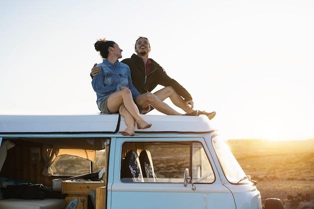 Casal feliz sentado em cima do telhado da minivan ao pôr do sol - jovens se divertindo nas férias de verão viajando ao redor do mundo - conceito de amor e férias - foco nos rostos