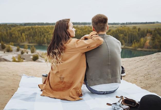 Casal feliz sentado em uma manta e apreciando a vista da natureza.