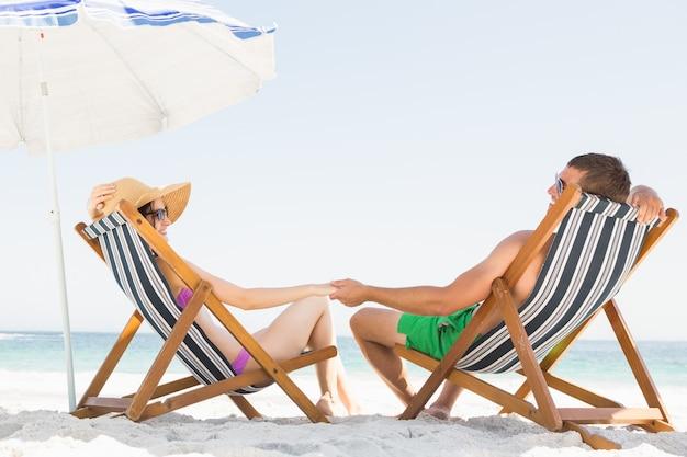 Casal feliz sentado na cadeira de praia