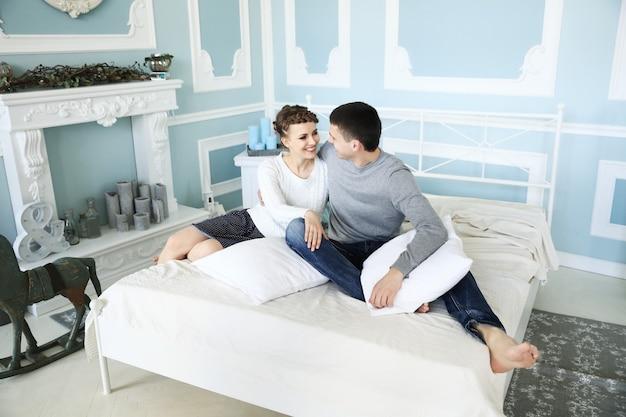 Casal feliz sentado na cama em um quarto espaçoso.