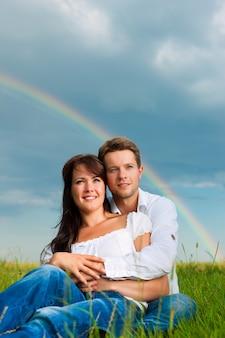 Casal feliz sentado na grama com arco-íris no fundo