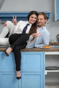 Casal feliz sentado na mesa da cozinha. alegre mulher bonita vestindo roupas formais, sentado no balcão da cozinha com o marido e fazendo sinais de paz com as duas mãos