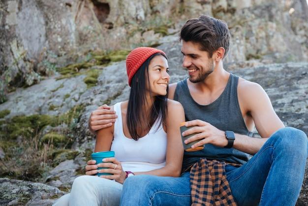 Casal feliz sentado na pedra olhando nos olhos um do outro