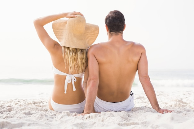 Casal feliz sentado na praia