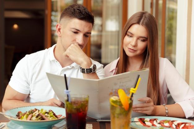 Casal feliz sentado no café e olhando para o menu