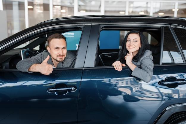 Casal feliz sentado no carro novo, showroom.