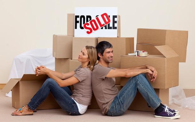 Casal feliz sentado no chão depois de comprar casa