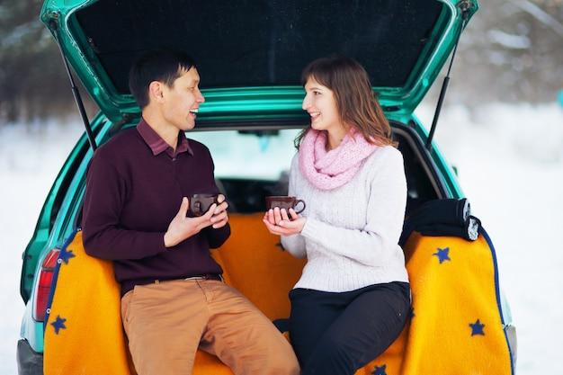 Casal feliz sentado no porta-malas aberto de um carro no inverno ao ar livre com canecas de chá quente nas mãos