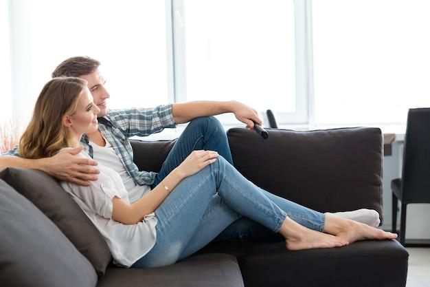 Casal feliz sentado no sofá na sala de estar assistindo tv