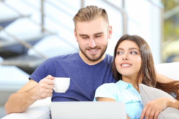 Casal feliz sentado no sofá tomando café e trabalhando em um laptop