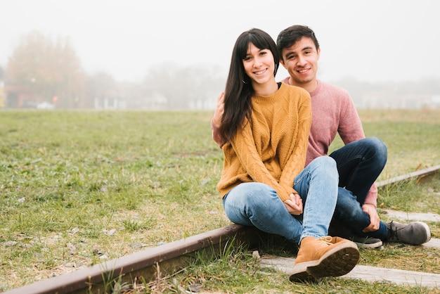 Casal feliz sentado nos trilhos e afago