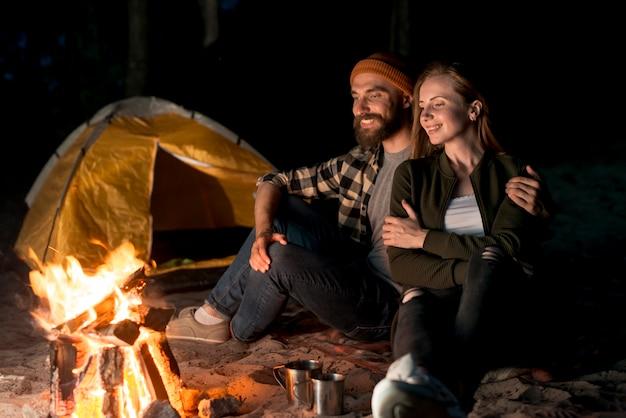 Casal feliz sentados juntos pela fogueira