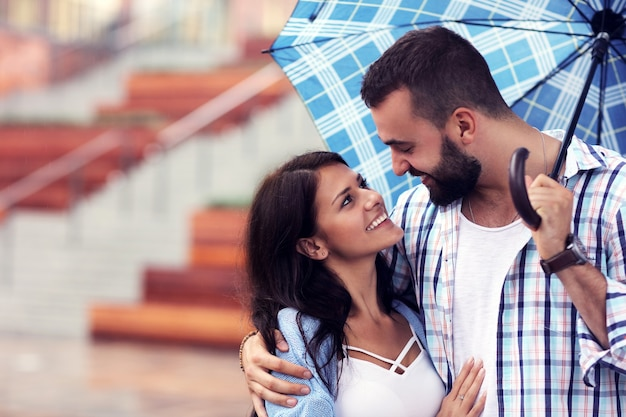 Casal feliz sob o guarda-chuva na cidade