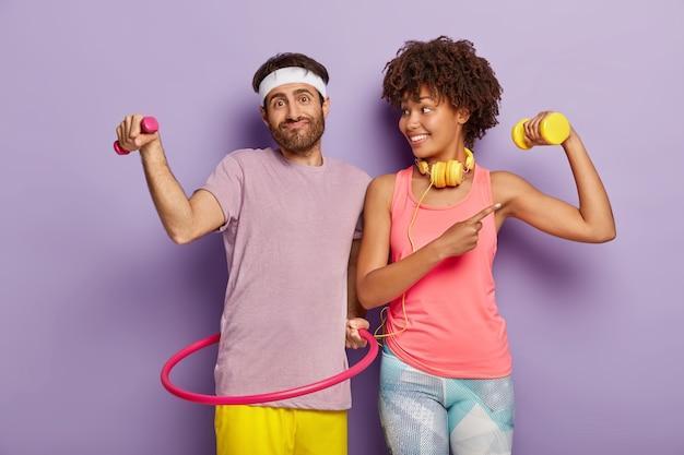Casal feliz tem treinamento, como esporte, homem com barba por fazer segura halteres, exercícios com bambolê, menina de pele escura satisfeita mostra bíceps, treina com peso, ouve música em fones de ouvido