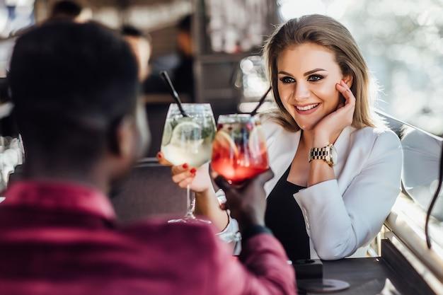 Casal feliz tendo momentos de ternura e bebendo coquetéis no bar do salão - jovens amantes se divertindo namoro em hotel clube de luxo.