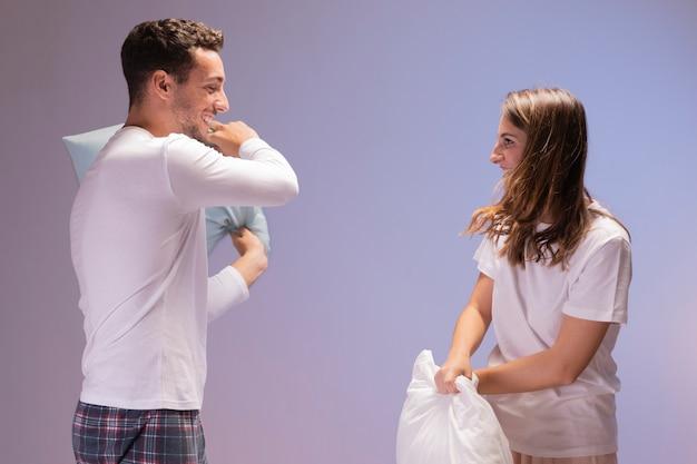 Casal feliz tendo uma luta de almofadas