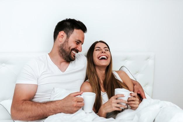 Casal feliz tendo uma xícara de café ou chá na cama.