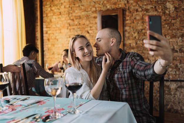 Casal feliz tira uma selfie no restaurante.