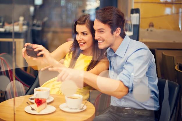 Casal feliz tirando foto em um café