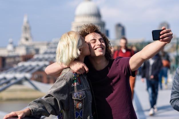 Casal feliz, tirando uma foto de selfie na ponte do milênio de londres