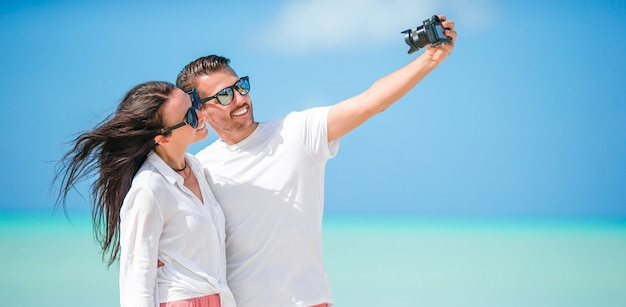 Casal feliz, tirando uma foto de selfie na praia branca. dois adultos curtindo suas férias na praia exótica tropical