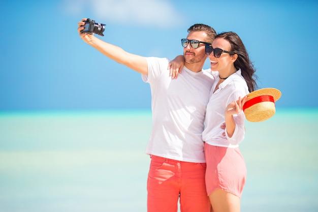 Casal feliz, tirando uma foto na praia branca de férias de lua de mel
