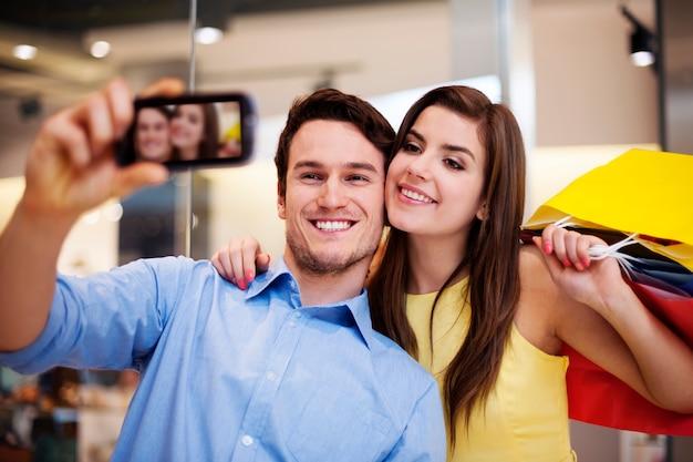 Casal feliz tirando uma foto no shopping