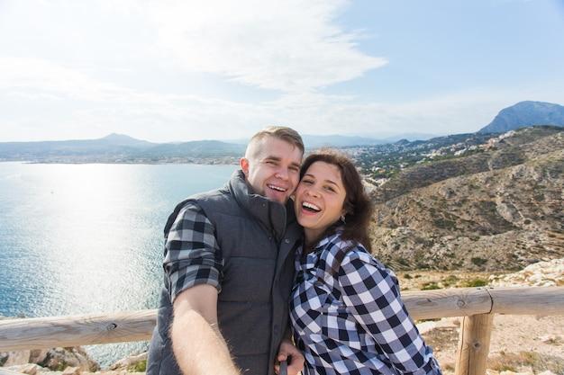 Casal feliz tirando uma selfie em uma bela paisagem
