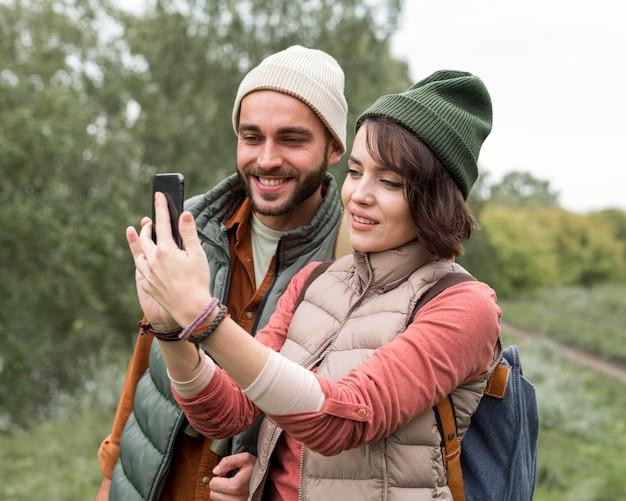 Casal feliz tirando uma selfie na natureza
