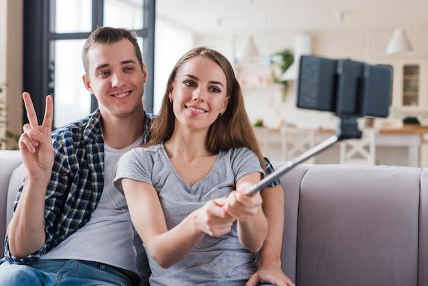 Casal feliz tiro selfie no apartamento