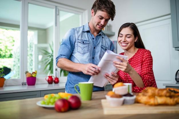 Casal feliz tomando café da manhã e lendo jornal em casa