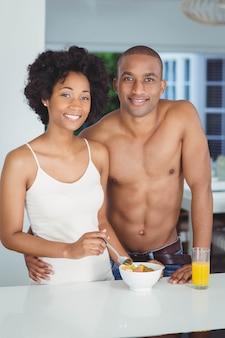 Casal feliz tomando café da manhã na cozinha em casa