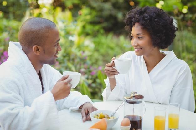 Casal feliz tomando café da manhã no jardim em casa