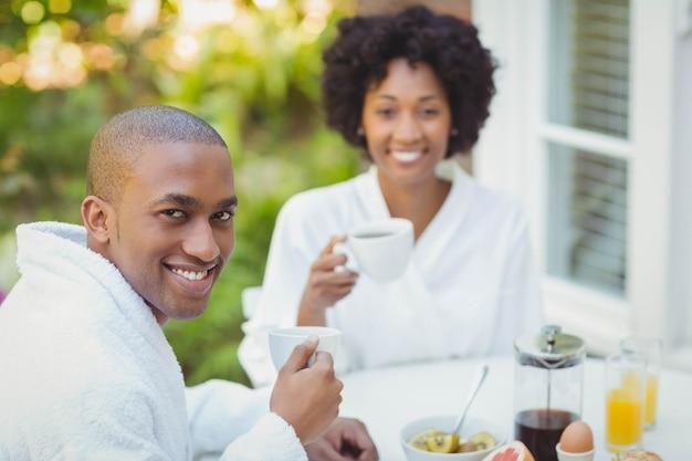 Casal feliz tomando café da manhã no jardim