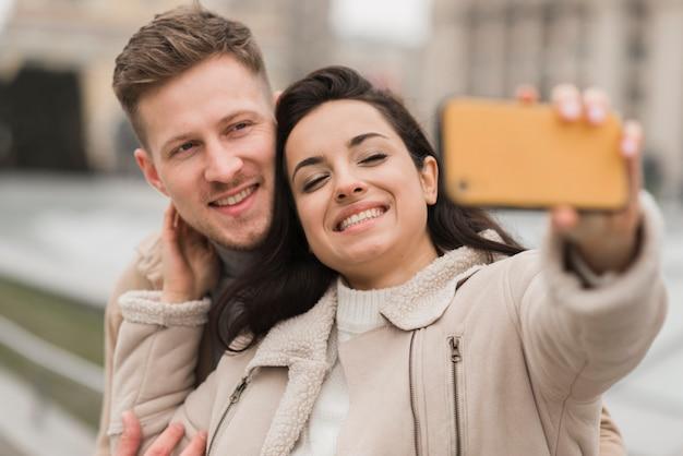 Casal feliz tomando uma selfie lá fora