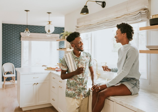 Casal feliz tomando uma taça de vinho na cozinha