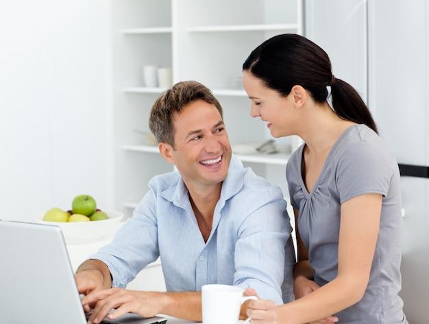 Casal feliz trabalhando em seu laptop na cozinha