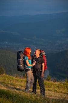 Casal feliz turista em pé na estrada nas montanhas