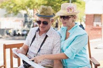 Casal feliz turista olhando mapa da cidade