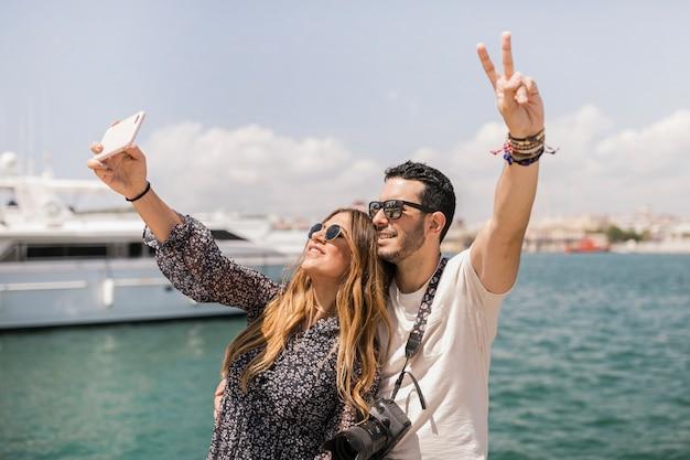 Casal feliz turista tomando selfie no celular contra o mar
