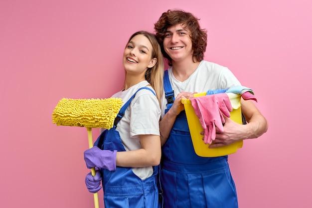 Casal feliz usa trapos e outras ferramentas para limpeza, posando para a câmera isolada sobre fundo rosa.