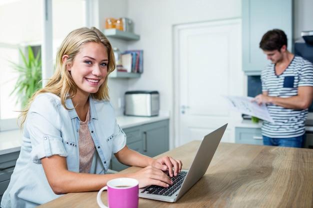 Casal feliz usando laptop e lendo na cozinha
