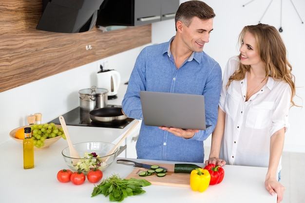 Casal feliz usando laptop e preparando pratos vegetarianos na cozinha de casa