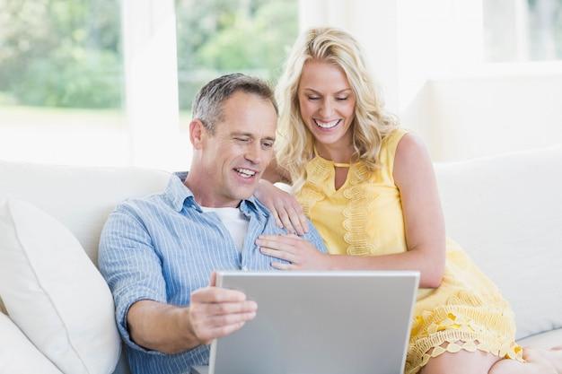 Casal feliz usando laptop no sofá na sala de estar
